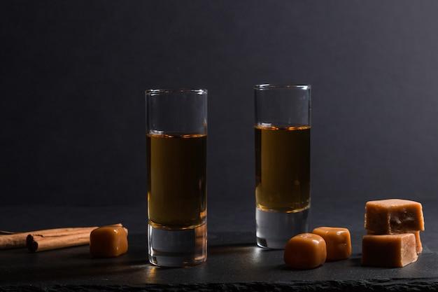 Glas whisky met karamelsuikergoed op een zwarte leisteenraad op zwarte achtergrond. zijaanzicht, low key.