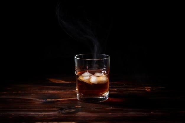 Glas whisky met rook en ijs op een houten tafel