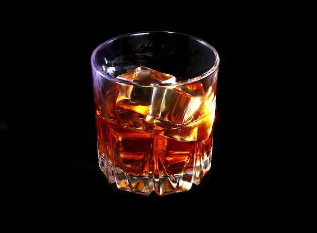 Glas whisky of bourbon met ijs op zwarte stenen tafel.