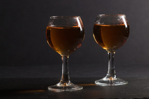 Glas whisky op een zwarte steen leisteen bord op zwarte achtergrond. zijaanzicht, rustig, close-up.