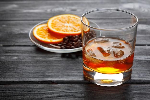 Glas whisky op ijs met fles op houten bar