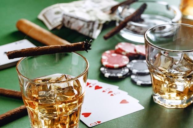 Glas whisky sigaar speelkaarten en chips op groene ondergrond