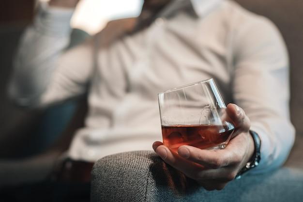 Glas whisky. vermoeide zakenman die wit overhemd draagt dat glas whiskyzitting in leunstoel houdt