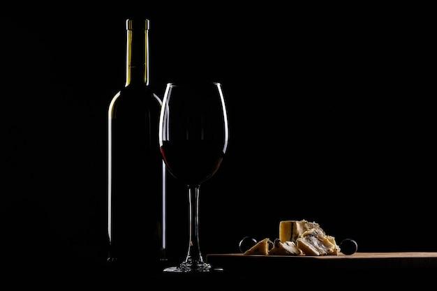 Glas wijn en fles, kaas met schimmel en druiven op zwarte achtergrond