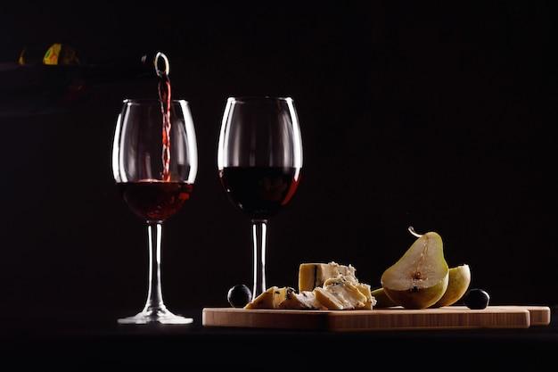 Glas wijn en fles, kaas met schimmel, peer en druiven op zwarte achtergrond