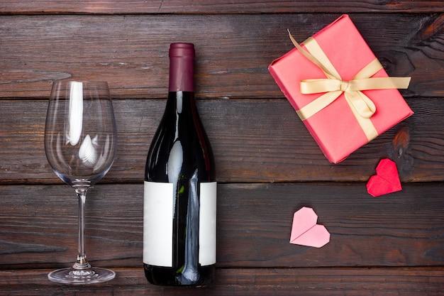 Glas wijn, fles rode wijn en roze cadeau op een donkere achtergrond.