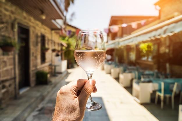 Glas wijn in de hand een glas jonge verse rose wijn tegen de achtergrond van een zomercafé in een me...