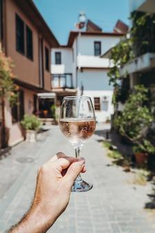 Glas wijn in de hand een glas jonge verse rose wijn tegen de achtergrond van een zomercafé