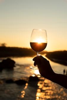 Glas wijn met stralende zon op de rug