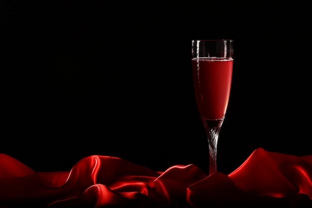 Glas wijn op rode zijde met donkere achtergrond