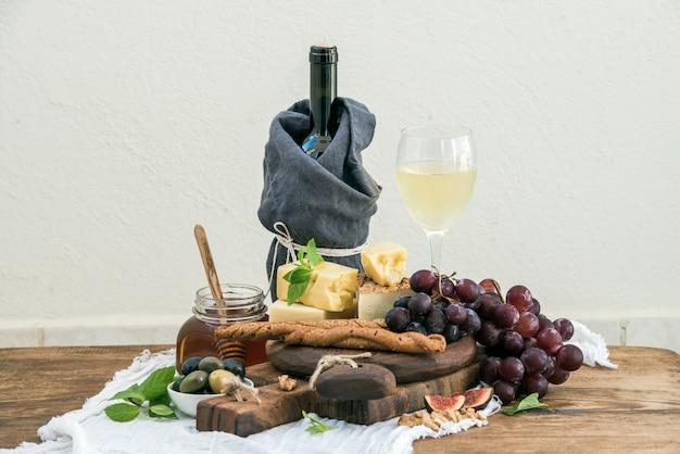 Glas witte wijn, kaasplank, druiven, vijgen, aardbeien, honing en broodstokjes op rustieke houten tafel, lichte muur