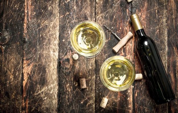 Glas witte wijn met een kurkentrekker. op een houten tafel.