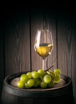 Glas witte wijn met een tros rijpe druiven