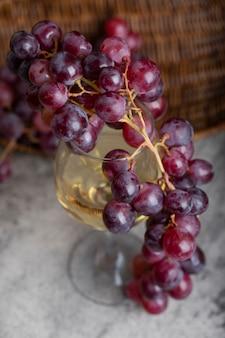 Glas witte wijn met verse rode druiven op stenen tafel.