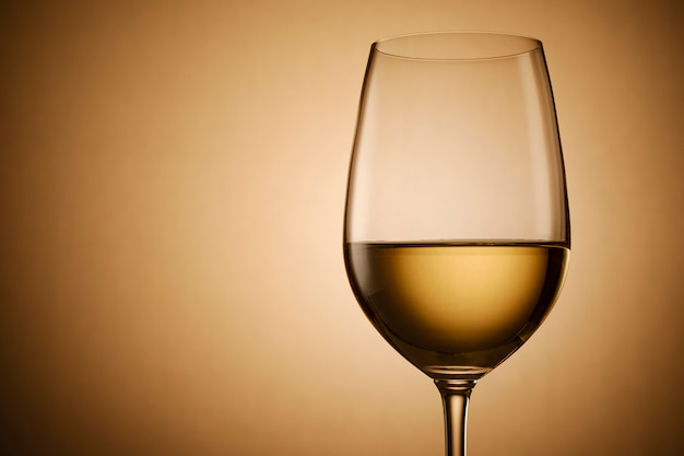 Glas witte wijn op gouden verloop