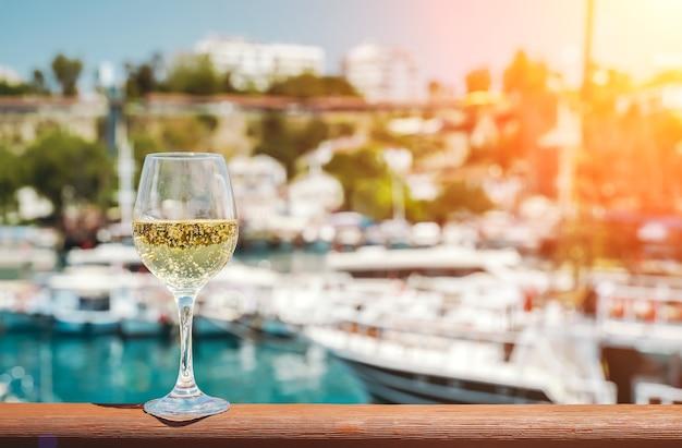 Glas witte wijn tegen de achtergrond van de middellandse zee en de haven met jachten in een rondvaart...