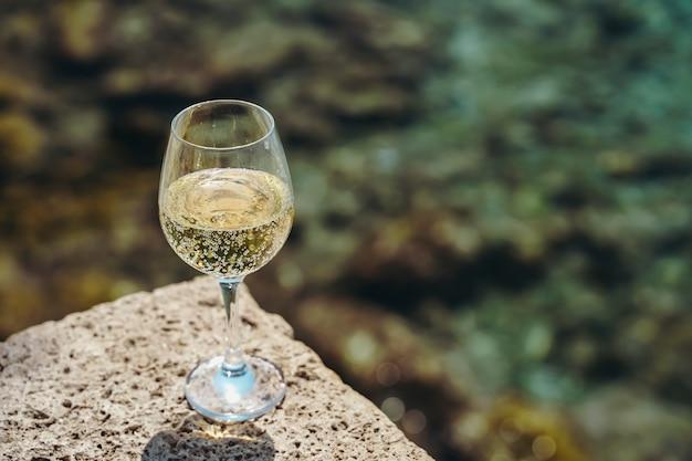 Glas witte wijn tegen de achtergrond van het mediterrane strand en de zee in een toeristisch stadje...
