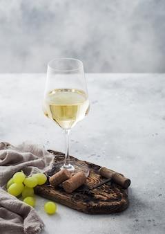 Glas witte zelfgemaakte wijn met kurken, kurkentrekker en druiven op een houten bord met linnen doek op lichte tafel achtergrond.