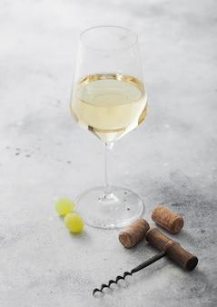 Glas witte zelfgemaakte wijn met kurken, kurkentrekker en druiven op lichte stenen achtergrond.