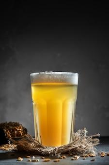 Glas zelfgemaakte bier op een concrete achtergrond. glas ambachtelijk bier op een donkere achtergrond.