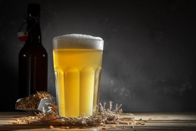 Glas zelfgemaakte bier op een houten tafel. glas ambachtelijk bier op een donkere achtergrond.