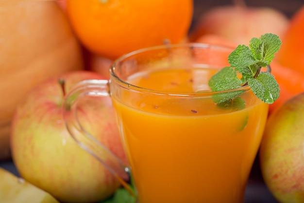 Glas zelfgemaakte sap of smoothie, fruit en groenten. verse wortel, appel, pompoen, sinaasappel, grapefruit op donkere tafel. gezond eten, eten, diëten, detox en vegetarisch concept.