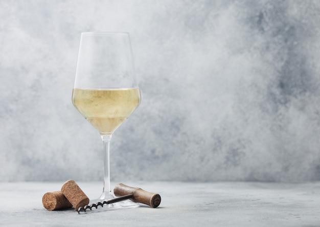 Glas zomer witte wijn met kurken en kurkentrekker op lichte tafel achtergrond.