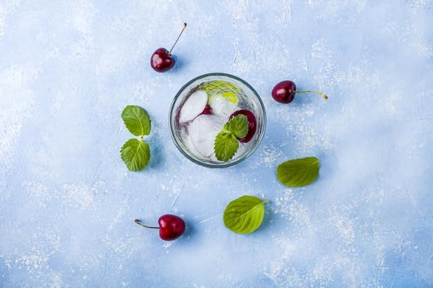 Glas zomerlimonade of ijsthee. verfrissend koel drankje met kers en munt op blauwe tafel. mojito cocktail met ijsblokjes.
