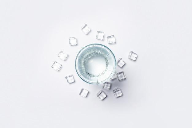 Glas zuiver kristalwater en ijsblokjes op een witte achtergrond onder zonlicht.