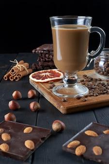 Glas zwarte koffie met melk met chocolade, hazelnoten, kaneelstokjes en plakjes gedroogde grapefruit