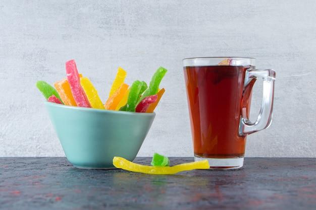 Glas zwarte thee met kom kleurrijke snoepjes op donkere ondergrond.