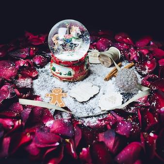 Glasbal met sneeuw en andere kerstversiering staat in de cirkel van rode rozenblaadjes