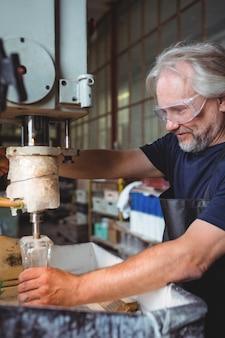Glasblazer die aan een glas werkt