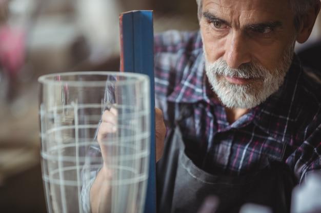 Glasblazer die aan een glaswerk werkt