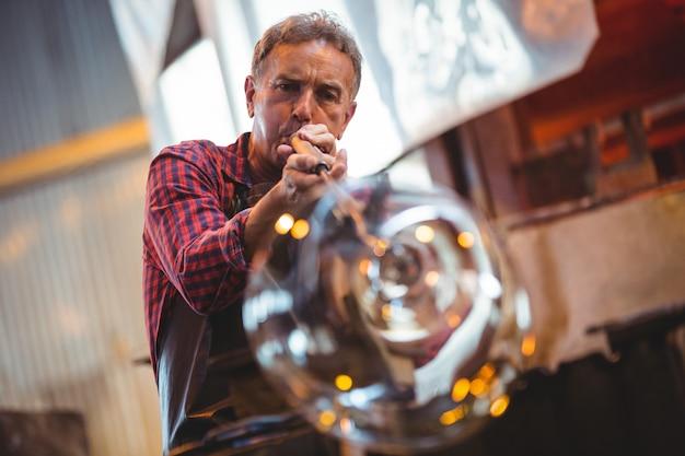 Glasblazer die een glas op de blaaspijp vormt