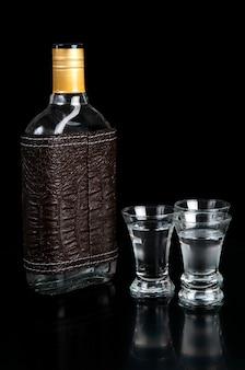 Glasfles en schot van wodka op een zwarte lijst
