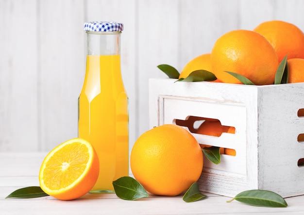 Glasfles organisch vers jus d'orange met ruwe sinaasappelen op witte houten doos