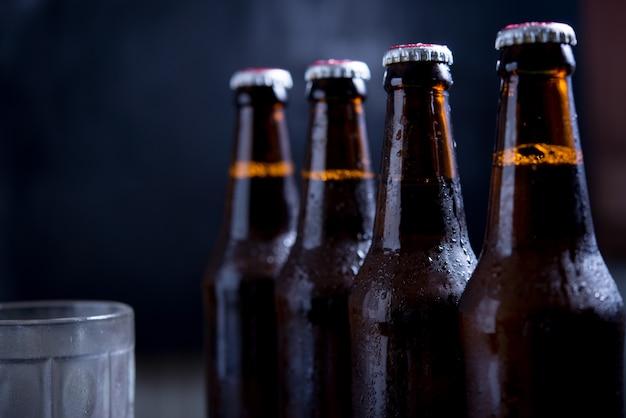 Glasflessen bier met glas en ijs op donkere achtergrond
