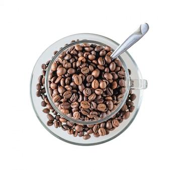 Glaskoffiebeker met geroosterde die koffiebonen wordt gevuld met lepel op wit wordt geïsoleerd