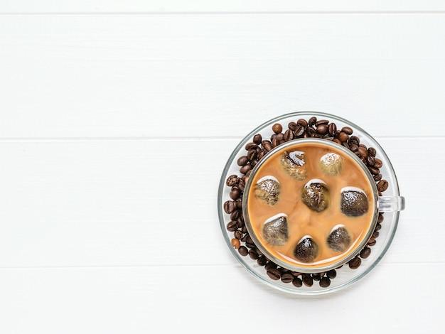 Glaskom met ijskoffie en koffiebonen op witte houten lijst. verfrissende en verkwikkende drank van koffiebonen en melk. het uitzicht vanaf de top. plat liggen.