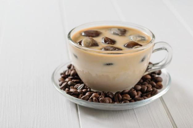 Glaskom met ijskoffie en koffiebonen op witte houten lijst. verfrissende en verkwikkende drank van koffiebonen en melk.