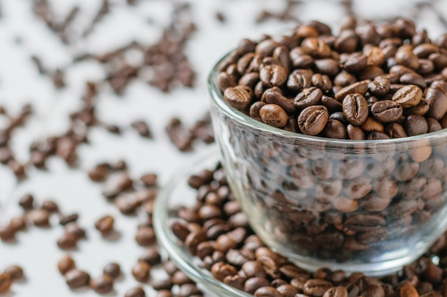 Glaskom met koffiebonen op witte lijstachtergrond met verspreide koffiebonen.