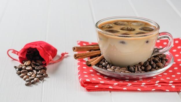 Glaskop met ijskoffie en koffiebonen die uit de zak op een witte lijst morsen. verfrissende en verkwikkende drank van koffiebonen en melk.