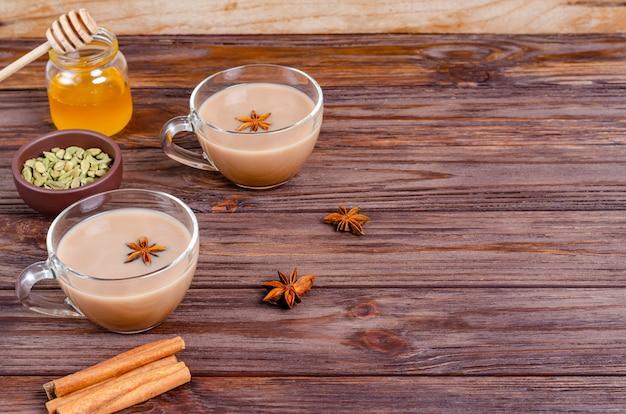 Glaskoppen van de traditionele indische thee van theemasala op houten oppervlakte