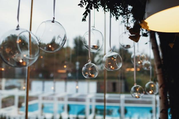 Glaskralen met kaarsen hangen voor het raam