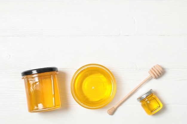 Glaskruik en kom met honing, beer op witte houten achtergrond. plat liggen