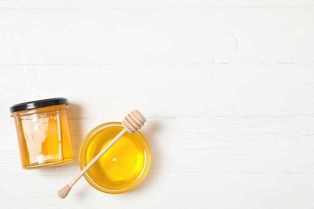 Glaskruik en kom met honing, dipper op witte houten achtergrond, ruimte voor tekst