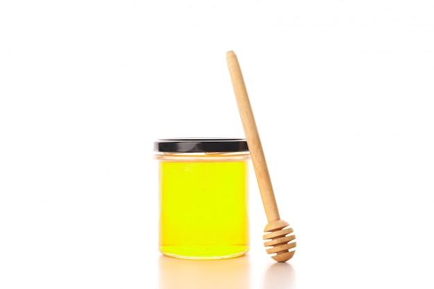 Glaskruik met honing en dipper op witte achtergrond wordt geïsoleerd die
