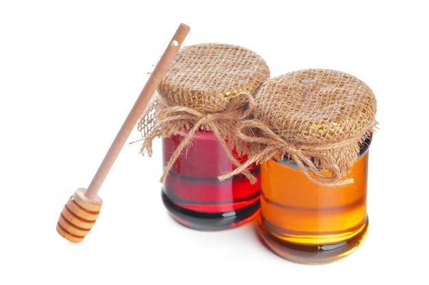 Glaskruik met zoete die honing op witte achtergrond wordt geïsoleerd