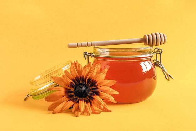 Glaskruik natuurlijke honing met houten drizzler en rudbeckia-bloem op gele achtergrond